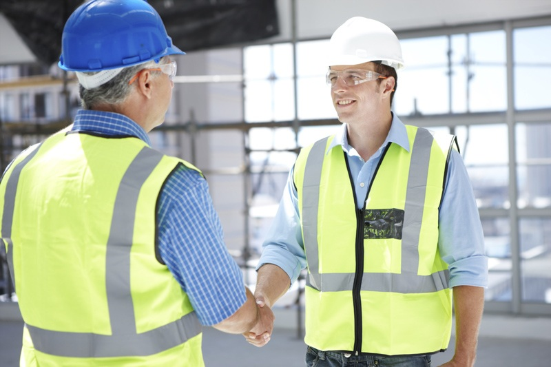Two engineers shaking hands on a construction site
